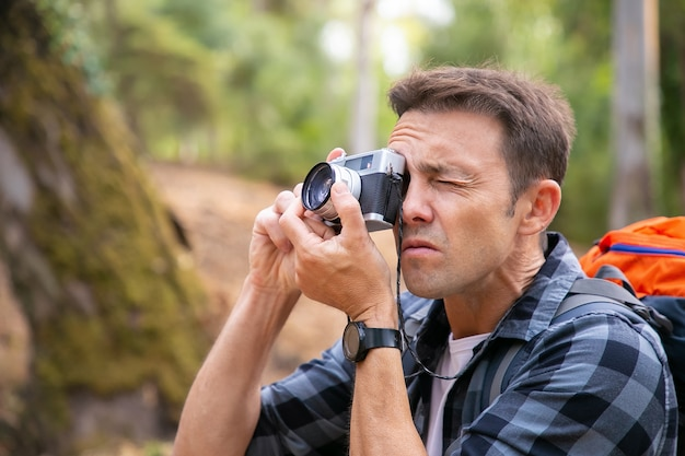 Focused man shooting landscape and walking in forest. caucasian traveler exploring nature, holding camera, taking photo and carrying backpack. tourism, adventure and summer vacation concept