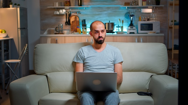 Focused man sitting on sofa and writing online project on laptop