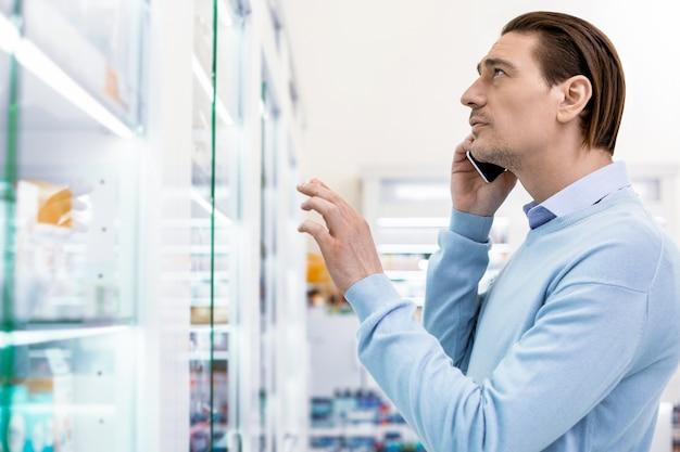 Сосредоточенный мужчина разговаривает по смартфону, стоящему перед большой стеклянной витриной, выбирая медицинский продукт