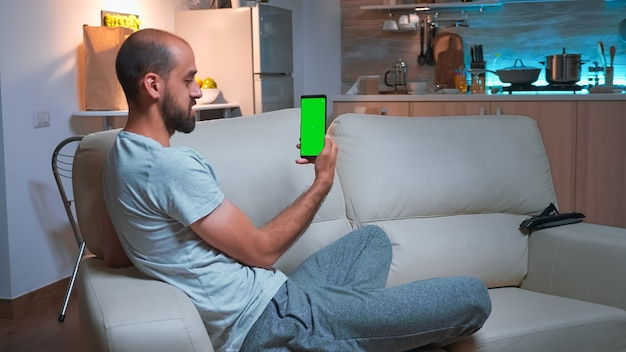 Focused man talking with his friends on smartphone with mock up green screen chroma key display. caucasian male using modern technology wireless while sitting on sofa late at night in kitchen