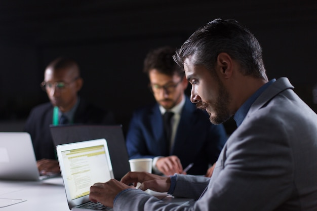 Focused man typing on laptop while working in office at night