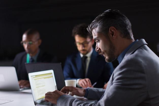 Сосредоточенный человек печатает на ноутбуке во время работы в офисе ночью