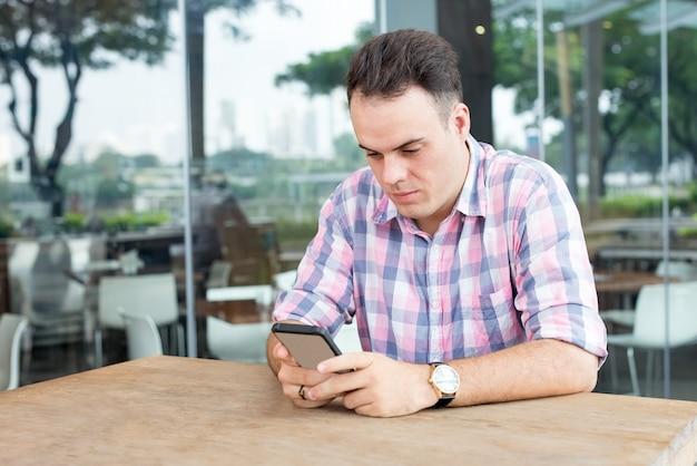 屋外のカフェでスマートフォンを使用する集中した男