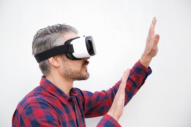 Focused man in vr headset moving hands