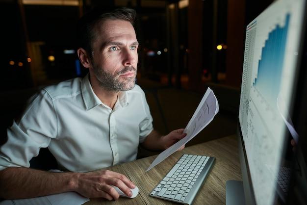 Сосредоточенный человек с документом с помощью компьютера