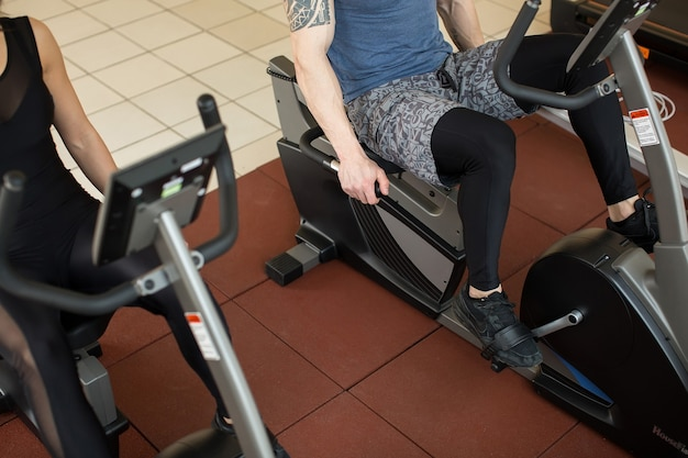 Focused man and woman on exercise bikes at the gym