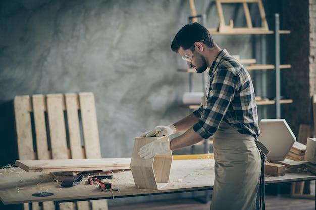 Сосредоточенный рабочий мужчина с деревянной полкой восстанавливает полировку поверхности мебели в домашнем гараже