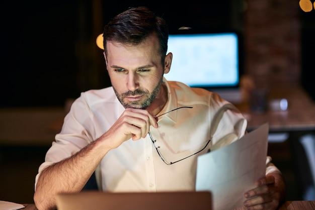 Сосредоточенный человек работает допоздна в своем домашнем офисе
