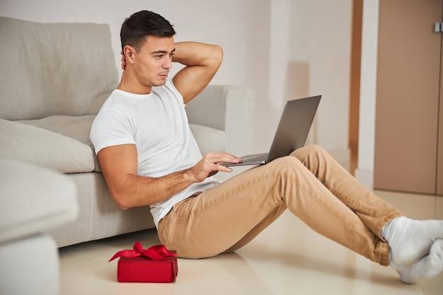 自宅から自分のコンピューターで作業している焦点を絞った男