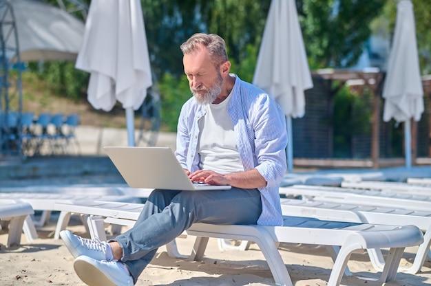 Сосредоточенный человек, работающий на ноутбуке на открытом воздухе