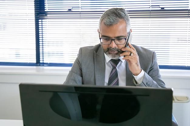 사무실에서 직장에서 컴퓨터를 사용하는 동안 휴대 전화에 말하는 성숙한 임원 집중. 전면보기. 디지털 커뮤니케이션 및 멀티 태스킹 개념