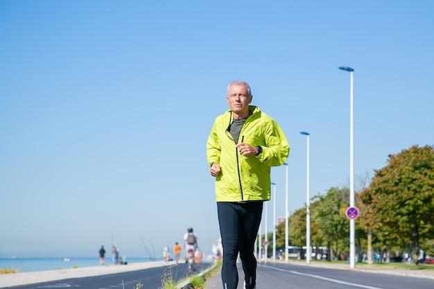Сосредоточенный зрелый мужчина в зеленой спортивной куртке и трико бегает трусцой вдоль берега реки снаружи. тренировка старшего бегуна для марафона. передний план. концепция активности и возраста