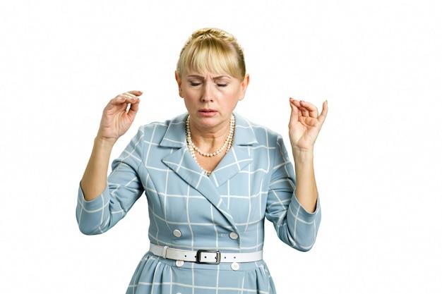 集中した成熟した女性が狂っている。白で瞑想する目を閉じた大人の女性。