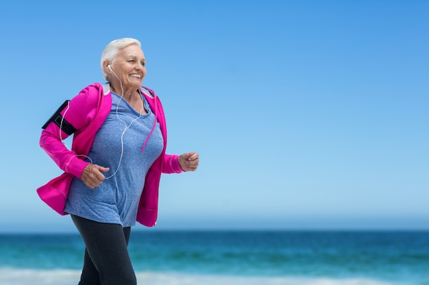Focused mature woman running and listening to music