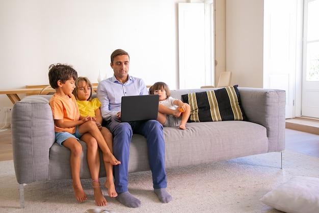 Papà di mezza età concentrato che si siede sul divano con i bambini e che scrive sul computer portatile. padre caucasico rilassante con bambini carini in soggiorno e guardare film. tecnologia digitale e concetto di paternità