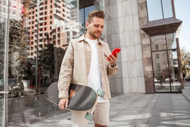 スマートフォンの投稿中に焦点を当てたミレニアル世代の金髪の男は、携帯電話のガジェット、ロングボードを保持している流行に敏感なスケートボーダーを介して通信する都会のストリートバックグラウンドの学生に立ってストリーミングが好きです