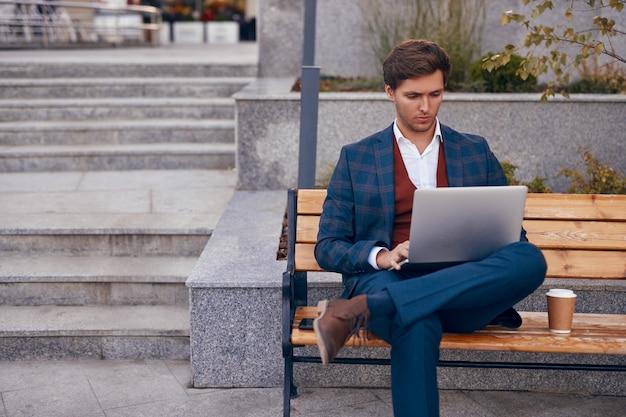 Сосредоточенный современный бизнесмен с кофе и ноутбуком на городской скамейке