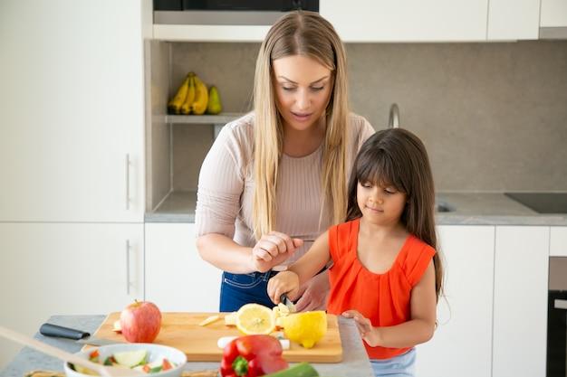 Сосредоточенная мама наблюдает, как ее девочка режет свежие овощи на разделочной доске. малыш помогает матери приготовить ужин. семья готовит вместе концепции