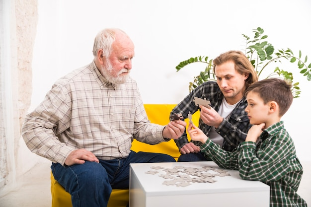 Focused multi-generational family assembling jigsaw puzzle together