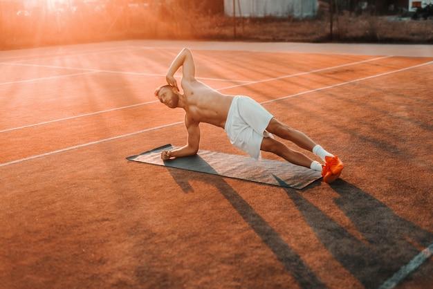 Сосредоточенный мускулистый бородатый человек, делающий боковые доски на теннисном корте утром летом.