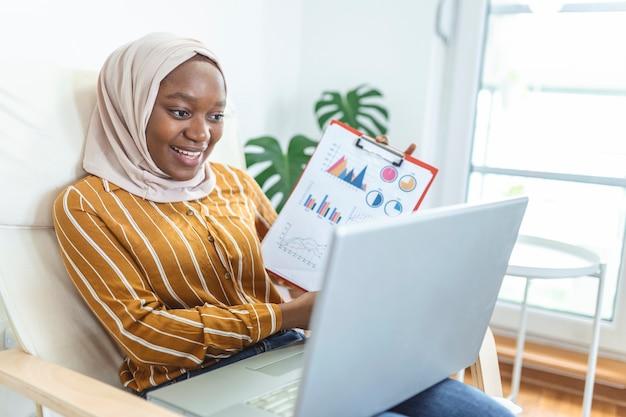 オンラインビデオ通話でチャートやグラフを提示する焦点を絞ったイスラム教徒の実業家。ラップトップでクライアントと電話会議をしている若いビジネスウーマンihヒジャーブ。屋内で作業するラップトップコンピューター。
