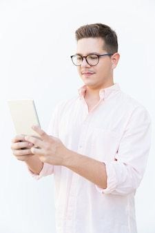 Focused nerdy guy in eyeglasses reading or watching content