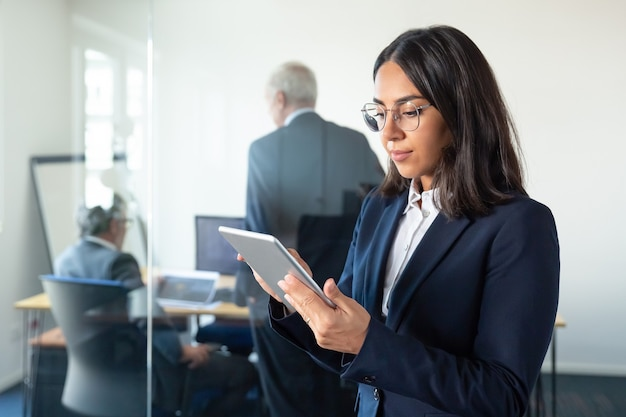 Focused office lady in glasses using tablet while two mature businessmen discussing work behind glass wall. copy space. communication concept