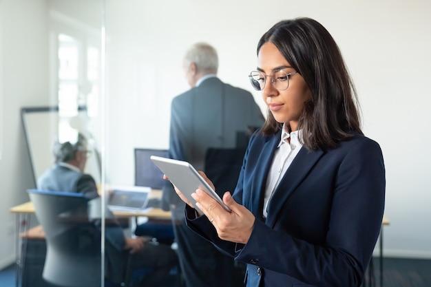 2人の成熟したビジネスマンがガラスの壁の後ろで仕事について話している間、タブレットを使用して眼鏡をかけているオフィスの女性に焦点を当てました。スペースをコピーします。コミュニケーションの概念