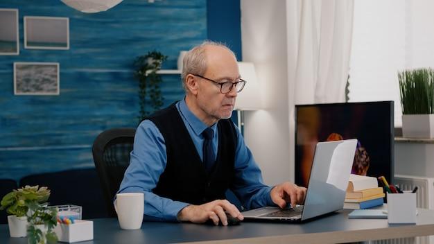 집중된 늙음 기업가 확인 그래픽 쓰기 랩탑 형 일하는 집 에서요 술 마시기 커피 retir.