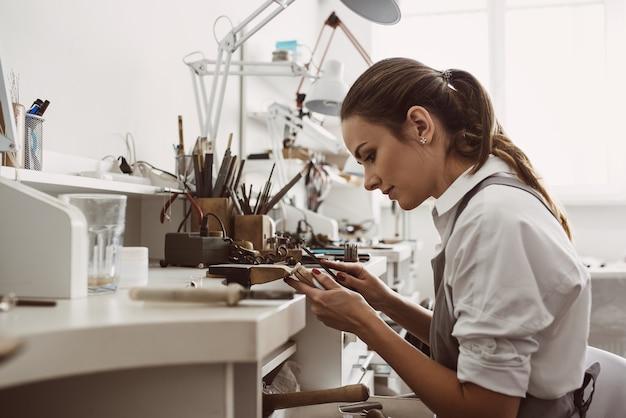 은반지 제작에 중점을 둔 젊은 여성 보석상의 과정 초상화에 중점을 둡니다.