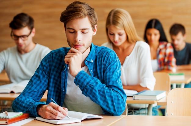 試験に焦点を当てた。教室の机に座ってメモ帳に何かを書いている集中した若い学生のグループ