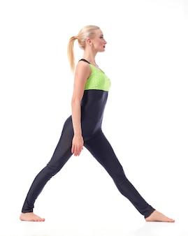 피트니스에 중점을 둡니다. 흰색 스포츠 체조 피트니스 개념에 고립 된 포즈 분할을 준비하는 여성 체조의 전체 길이 스튜디오 샷