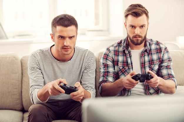 ゲームに焦点を当てています。ソファに座ってビデオゲームをプレイする2人の集中した若い男性