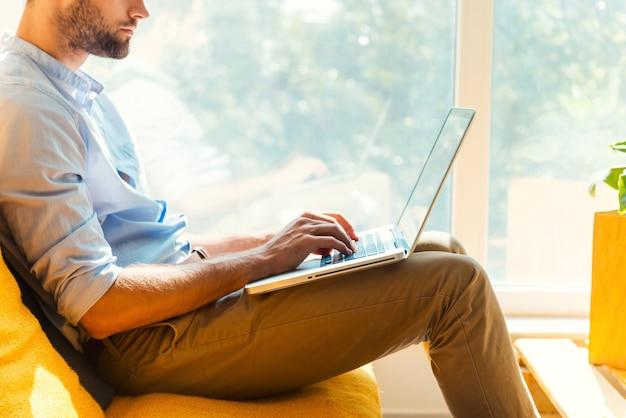 彼の仕事に焦点を当てた。オフィスの休憩所に座ってラップトップで作業している若い男のクローズアップ