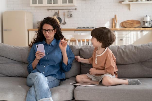 휴대 전화에 초점을 맞춘 젊은 어머니는 근처 소파에 앉아 지루한 작은 아이 아들에 관심을 기울이지 않습니다