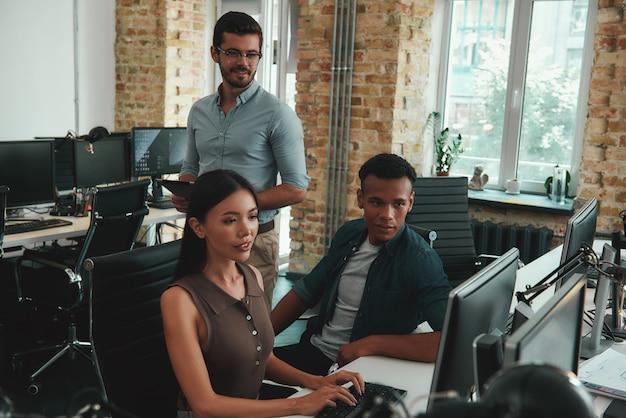Сосредоточено на рабочей группе молодых сотрудников, смотрящих на монитор компьютера и обсуждающих что-то во время