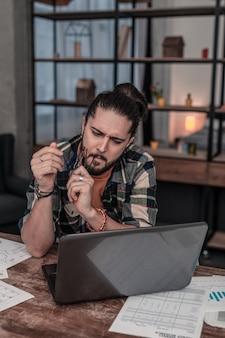 Сосредоточен на работе. серьезный молодой человек, держащий очки, глядя на экран ноутбука