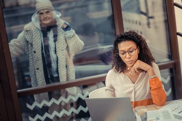 仕事に焦点を当てた。彼女の仕事に集中しながらノートパソコンの画面を見ている賢い若い女性