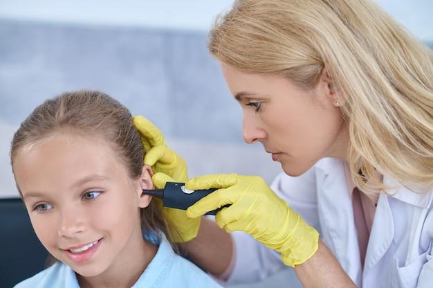 Focused otolaryngologist examining ear of smiling girl
