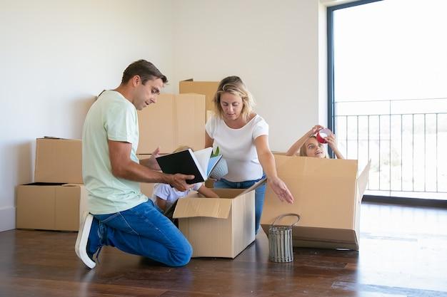 Сосредоточенные родители и веселые дети распаковывают вещи в новой квартире, сидят на полу и достают предметы из открытого ящика