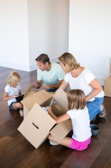 Сосредоточенные родители и дети распаковывают вещи в новой квартире, сидят на полу и берут предметы из открытых ящиков