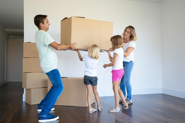 Сосредоточенные родители и две девочки вместе несут коробки в новую пустую квартиру