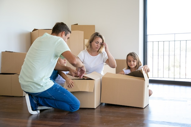 Focused parents and kids unpacking things in new apartment, sitting on floor and opening boxes