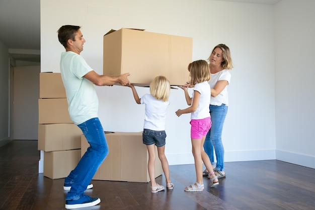 Focused parents and two girls carrying boxes into new empty flat together