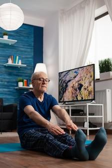 Сосредоточенный пенсионер в спортивной одежде сидит на коврике для йоги и растягивает мышцы ног