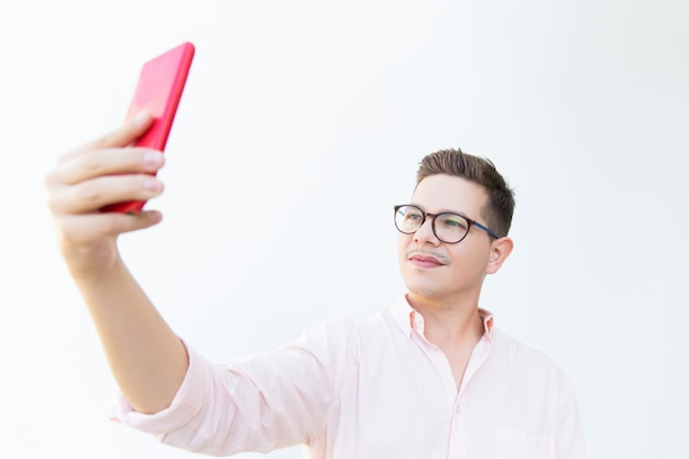 Focused pensive guy in eyeglasses taking selfie