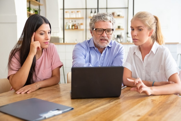 Focused pensive young woman and mature man meeting with female professional, watching and discussing content on laptop