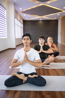 Focused people meditating at yoga class