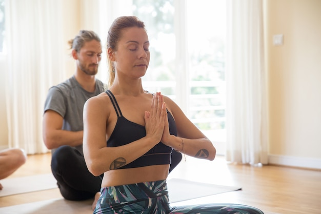 Focused people meditating at yoga class