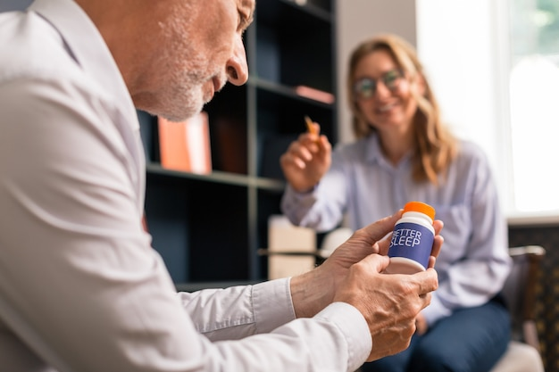 Focused person. closeup portrait of a concentrated man looking at a box of sleeping pills in his hands while sitting in front of a smiling woman during the therapy session